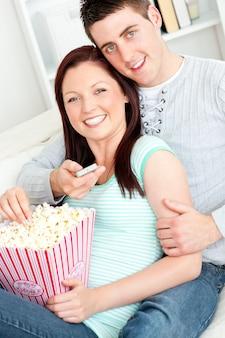 Pareja abrazándose comiendo palomitas de maíz y viendo la televisión tumbada t