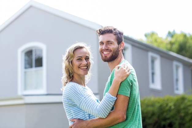 Pareja abrazándose contra casa