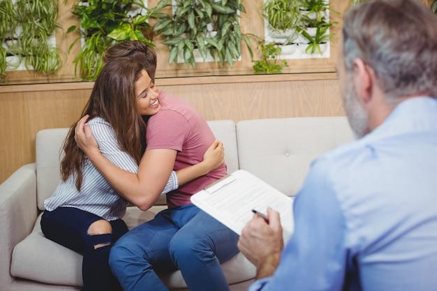 Pareja abrazándose mientras consulta al médico
