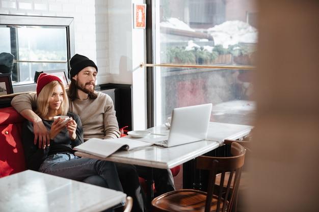 Pareja abrazándose y sentado en la cafetería