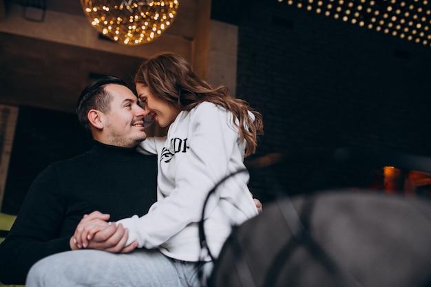 Pareja abrazándose y sentados juntos dentro de un café