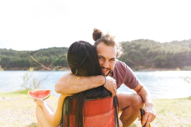 Pareja, se abrazar, en, orilla del río