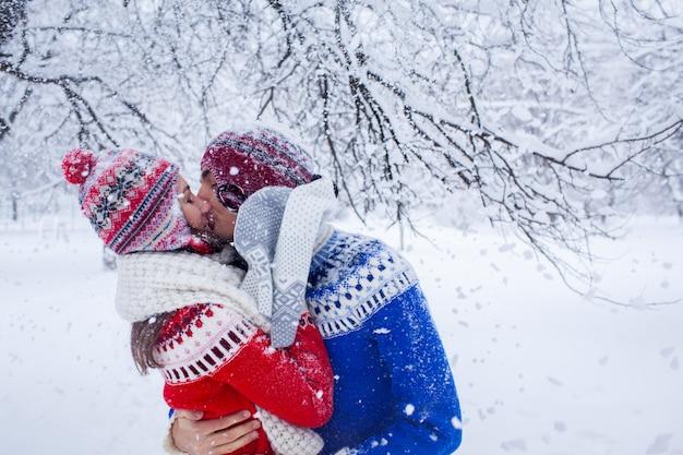 Pareja abrazos y besos en bosque de invierno