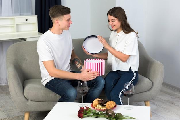 Pareja abriendo una gran caja de regalo en el sofá