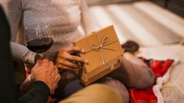 Pareja abriendo regalos junto con una copa de vino