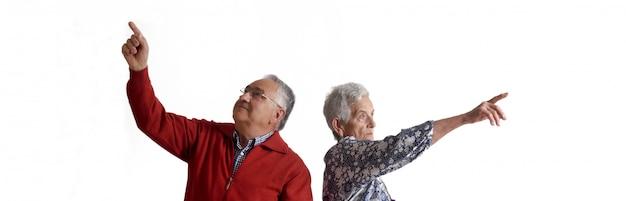 Una pareja de abuelos señalando con el dedo.
