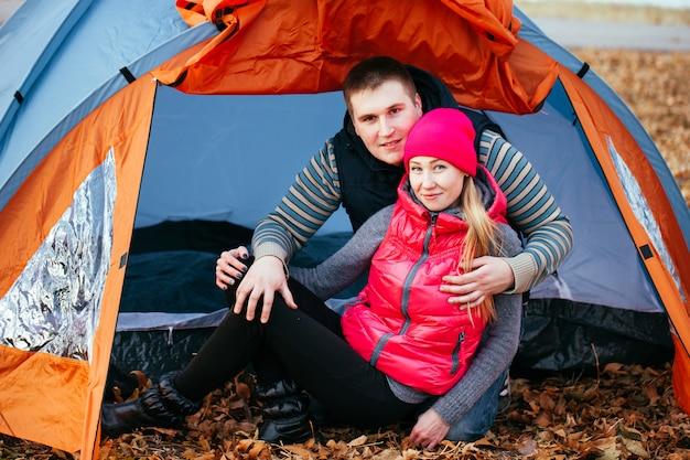 Pareja acampando. joven pareja sentada cerca de la tienda.
