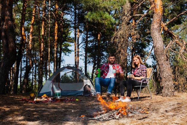 Pareja acampando y momento relajante