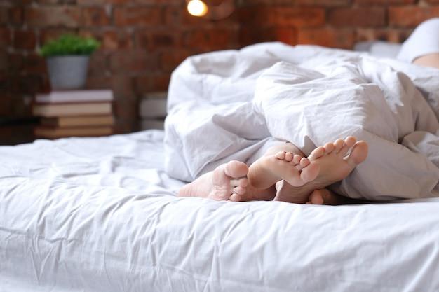 Pareja acostada en la cama en pijamas gemelas, vista de pies