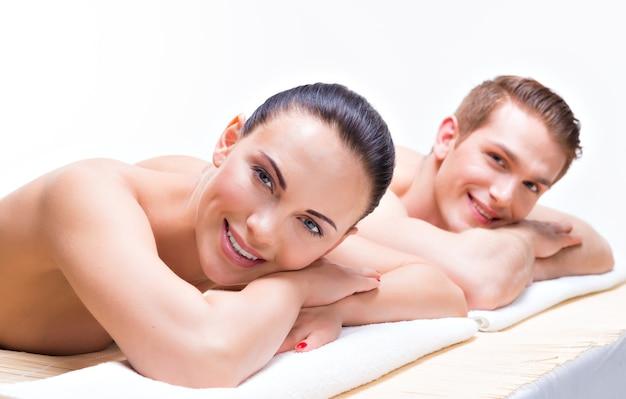 Pareja acostada en las mesas de masaje en el salón de spa. concepto de tratamiento de belleza.