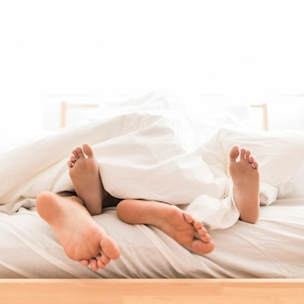 Pareja, acostado, descalzo, en cama
