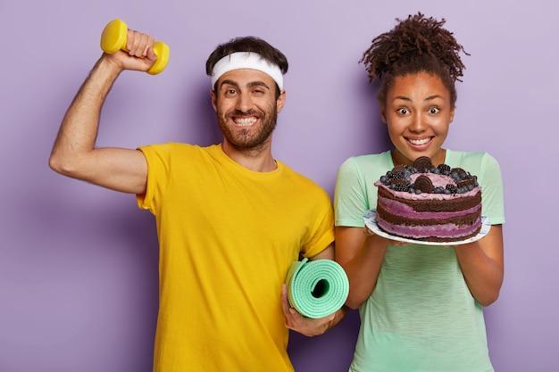 Pareja activa alegre posando con un gran pastel