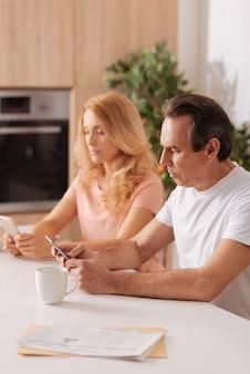 Pareja adictiva y sin emociones que se sienta en casa y usa teléfonos inteligentes sin prestar atención el uno al otro