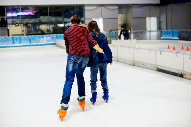 Pareja adolescente cogidos de la mano y patinaje sobre hielo juntos