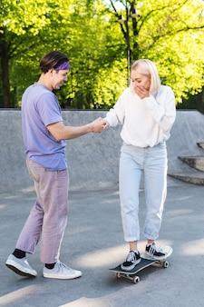 Pareja adolescente despreocupada en un parque de patinaje.
