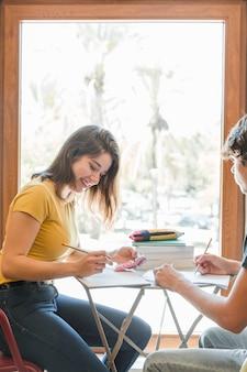 Pareja adolescente haciendo la tarea junto a la ventana