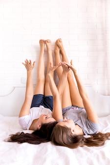 Pareja adolescente con pies y manos arriba