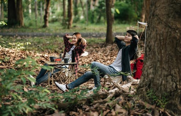 Pareja de adolescentes asiáticos jóvenes tienen tiempo de relajación con viaje de campamento, están sentados y con las manos en la parte posterior del cuello en una silla frente a la tienda de campaña con mochila en el parque natural