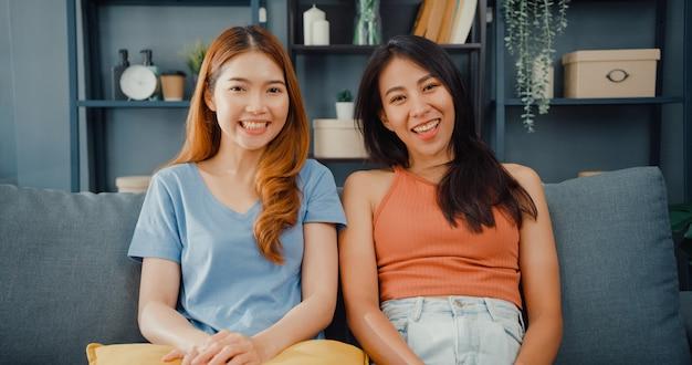 Pareja de adolescentes mujeres asiáticas que se sienten felices sonriendo y mirando al frente mientras se relajan en la sala de estar en casa