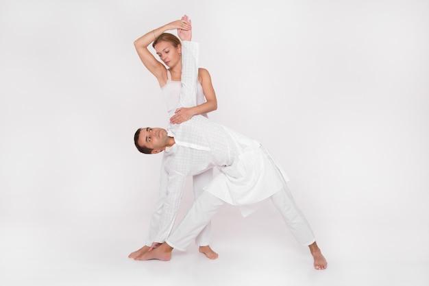 Pareja adulta dedicada al yoga, entrenamiento emparejado