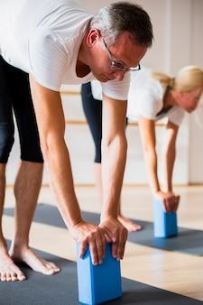 Pareja adulta entrenando con bloques de pilates