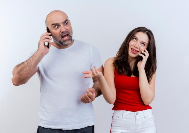 Pareja adulta hablando por teléfono impresionado hombre mirando al lado y mujer despistada mirando hacia arriba