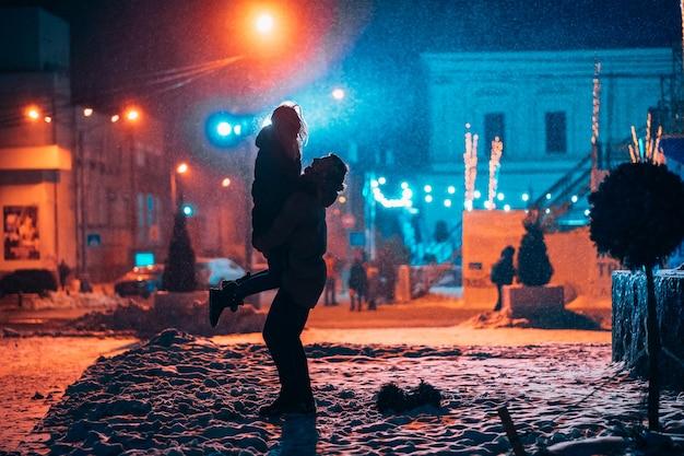 Pareja adulta joven en los brazos del otro en la calle cubierta de nieve