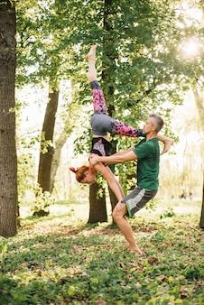 Pareja adulta media sana haciendo ejercicios de yoga acrobático en el parque