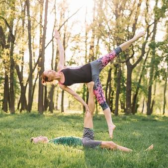Pareja adulta media sana practicando acro yoga en pasto