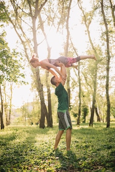 Pareja adulta media utilizando trucos acrobáticos en el parque