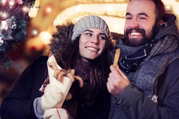 Pareja adulta pasando el rato en la ciudad durante la época navideña