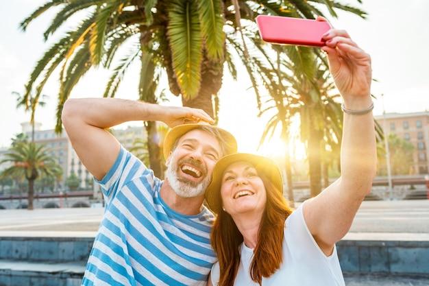 Pareja adulta saliendo y tomando una selfie en barcelona al atardecer