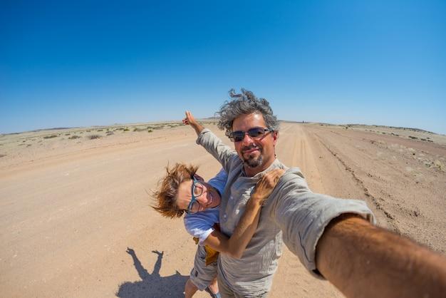 Pareja adulta tomando selfie en el desierto de namib, namib naukluft national park, namibia, áfrica.