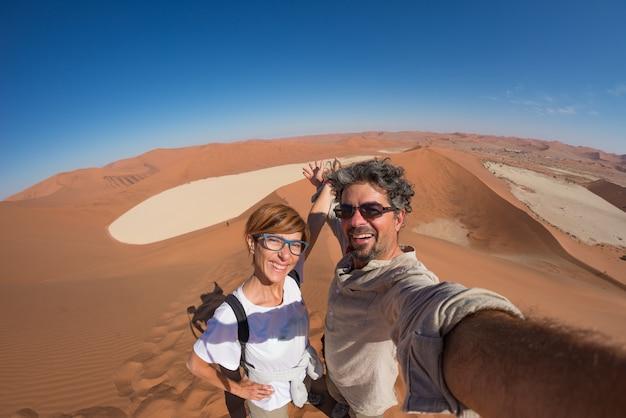Pareja adulta tomando selfie en dunas de arena en sossusvlei en el desierto de namib