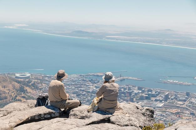 Pareja de adultos europeos en sombreros admirando la vista de ciudad del cabo y el océano desde la cima de la montaña de la mesa en ciudad del cabo, sudáfrica