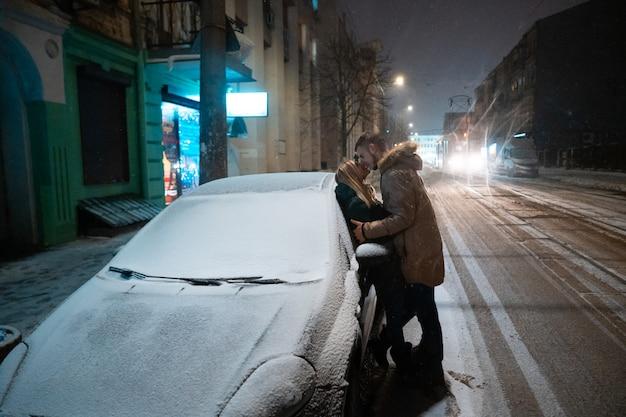 Pareja de adultos jóvenes besándose en la calle cubierta de nieve