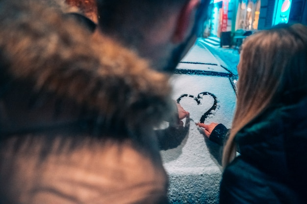 Pareja de adultos jóvenes dibuja un corazón en coche cubierto de nieve