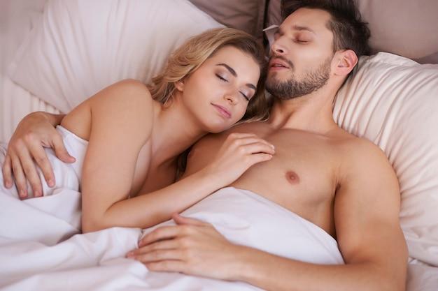 Pareja de adultos jóvenes durmiendo en el dormitorio