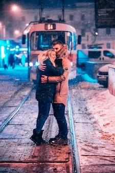 Pareja de adultos jóvenes en la línea de tranvía cubierto de nieve