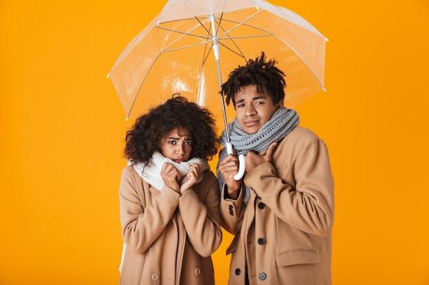 Pareja africana congelada vistiendo ropa de invierno de pie bajo un paraguas aislado