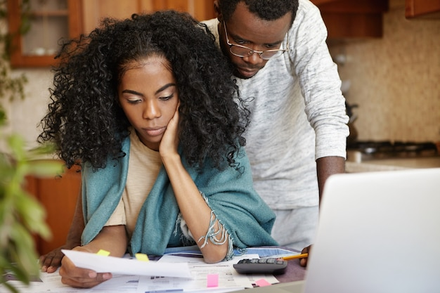 Pareja africana estresada que tiene muchas deudas tratando de reducir sus gastos domésticos para ahorrar dinero