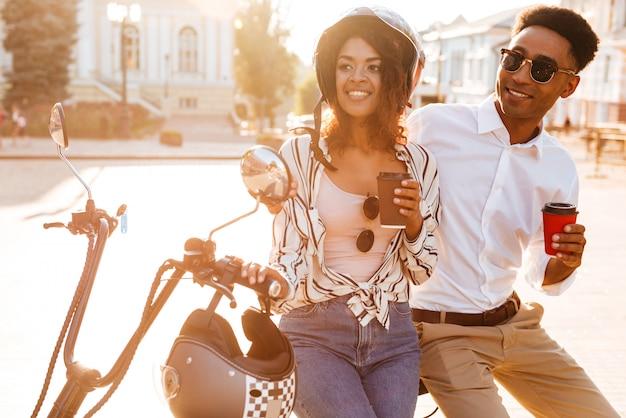 Pareja africana joven contenta tomando café mientras está de pie cerca de la moto moderna en la calle y mirando a otro lado