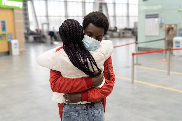 Pareja africana usa máscaras faciales abrazándose en la terminal del aeropuerto