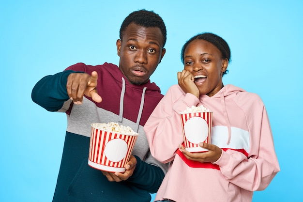 Pareja africana viendo una película con palomitas de maíz