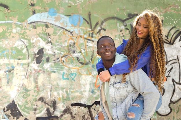 Pareja afro americana enfrente de muro de graffiti