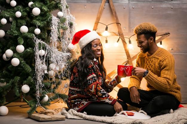 Pareja afroamericana, bebida, café, por el árbol de navidad