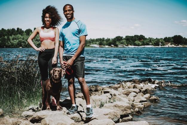 Pareja afroamericana caminando perro por río