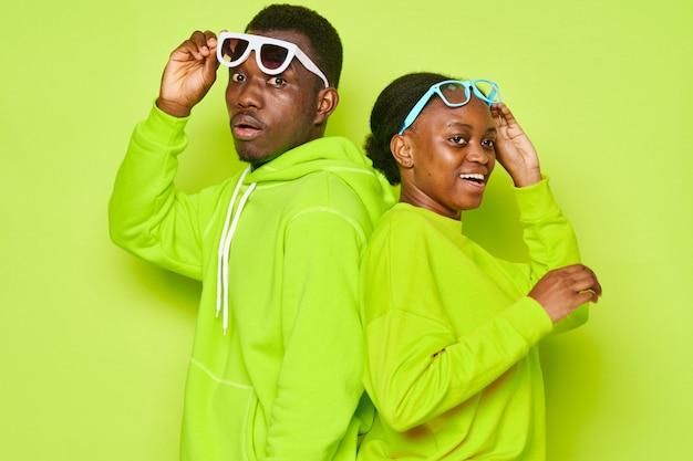 Pareja afroamericana en chándales verdes y gafas