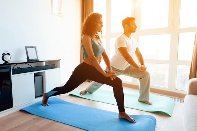 Pareja afroamericana haciendo ejercicios de yoga en casa