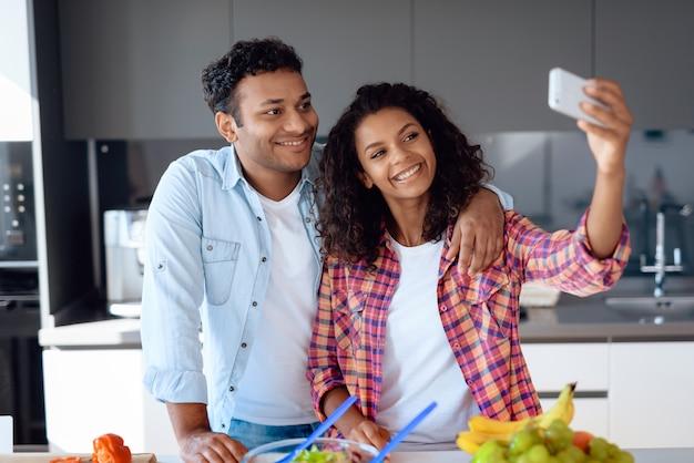 Pareja afroamericana haciendo selfie en cocina